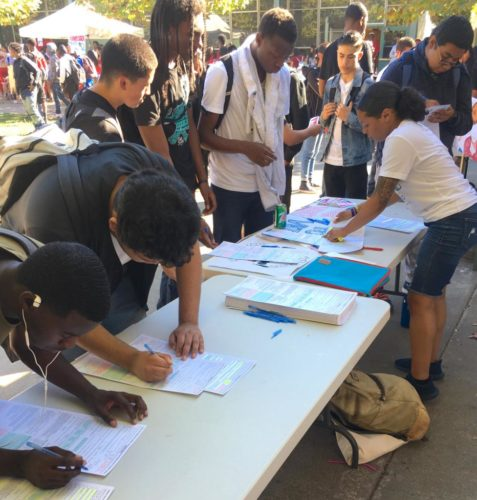 Oakland Rising's youth organizer registers young people at a table outside