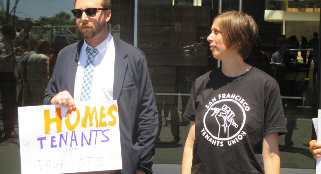 "A man in a suit jacket and tie holds a sign that says ""Homes 4 Tenants Not Tourists"" and a woman wears a T-shirt that says ""San Francisco Tenants Union"" and holds a sign below the frame of the photo."