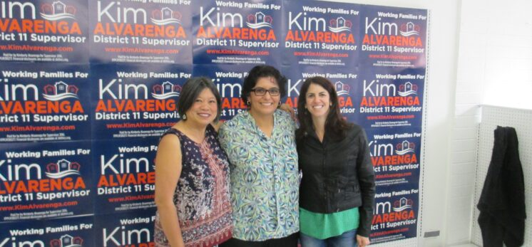 "Three women (L-R: Sandra Lee Fewer, Kimberly Alvarenga, and Hillary Ronen) stand in front of a ""selfie wall"" covered with Kim Alvarenga campaign signs"
