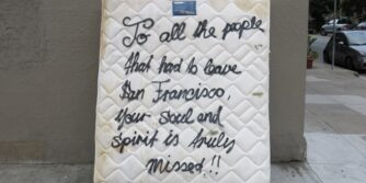 "Mattress against a wall that says, ""To all the people that had to leave San Francisco, your soul and spirit is truly missed!!"""