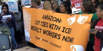 "Protestors holding up an orange banner that says ""Amazon: Cut Ties With ICE! Respect Workers Now!"""