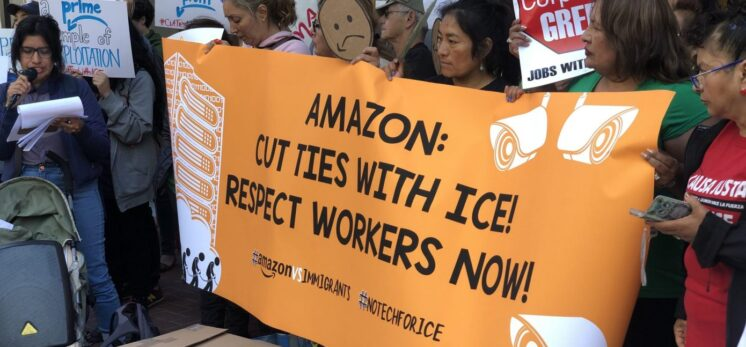 """Protestors holding up an orange banner that says """"Amazon: Cut Ties With ICE! Respect Workers Now!"""""""
