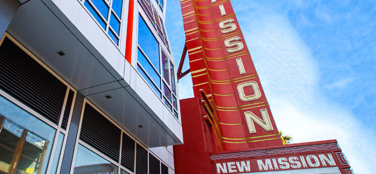 Picture of the New Mission Theater marquee with a modern, colorful building behind it
