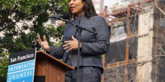 "San Francisco mayoral candidate London Breed stands at a podium with a sign on the front that says ""San Francisco Interfaith Council"""