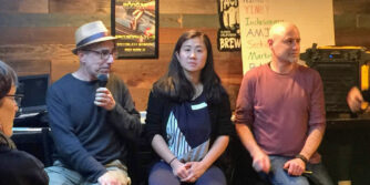 A man with a microphone, a woman, and another man seated at a community event at a bar