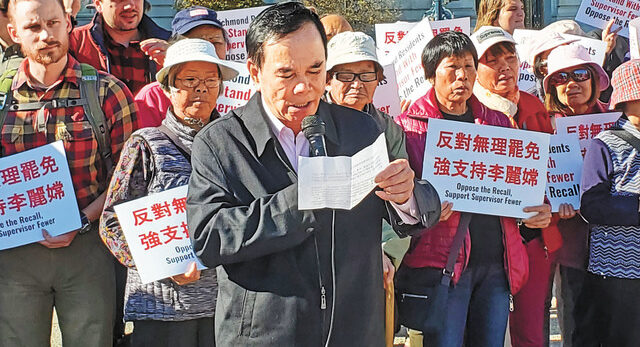 Protestors holding signs in an Asian language, with a man in the front reading from a sheet of paper